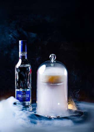 Odessa, Ukraine. February 07, 2020. Bottle of vodka Finlandia. Secret cocktail under a cap filled with smoke. tasty cocktails on dark background with smoke and light
