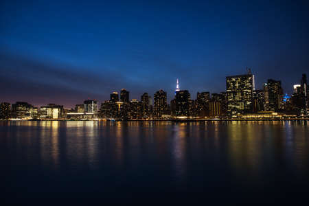 New York City panorama with Manhattan skyline over East River at night