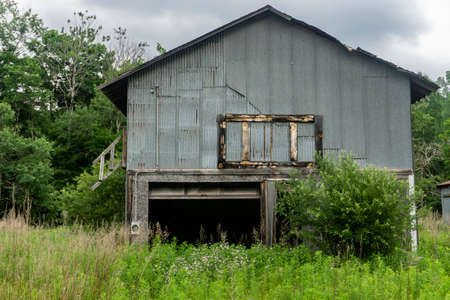 Side of an aged and worn exterior of abandoned house or storage place close to the woods 写真素材