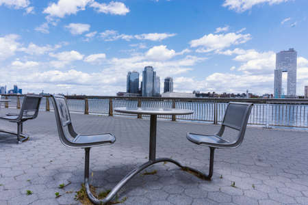 Chairs and table on a promenade along East River in Manhattan with a view of Brooklyn