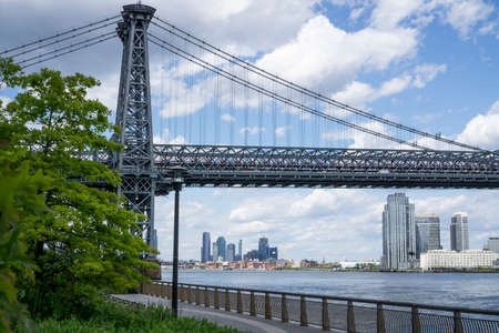 An empty promenade along East River in lower Manhattan with a view of Williamsburg Bridge