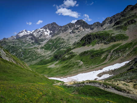Mountain grassy ranges with rocky hills and snow. Trekking in summer
