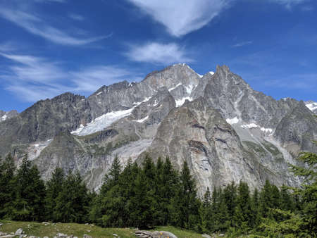 A scenic view of Alpine mountains on a beautiful sunny day. Rocky hills. Meadows, trekking pathway