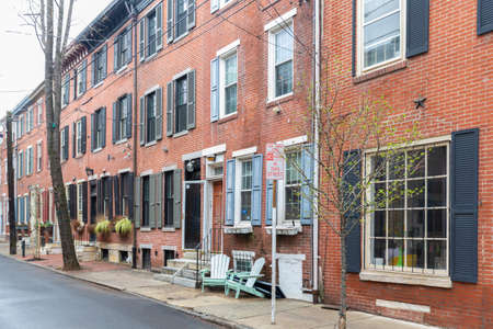 Rows of brownstone apartment buildings in Center City with chairs, stoops and planters in Pennsylvania
