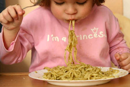 little child eating pasta with pesto sauce
