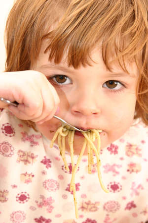 gluttonous: little cute girl eating spaghetti with pesto sauce