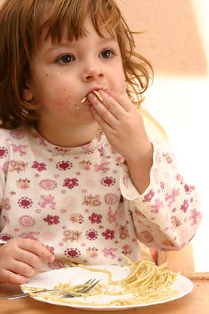 little cute girl eating spaghetti with pesto sauce