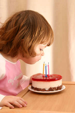 children celebration: little girl and her birthday cake with candles