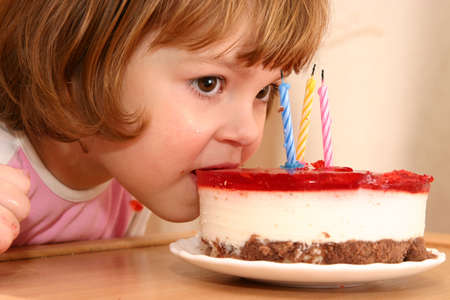 little girl taking a mouthful of her birthday cake