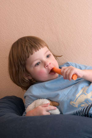 little girl eating healthy carrot