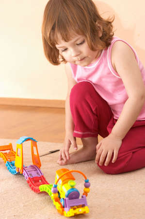 little cute girl while playing with toy train