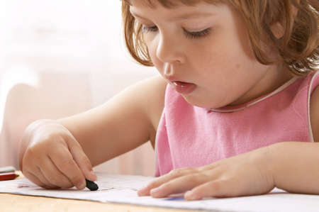 concentrated: little, cute preschool girl concentrated on drawing