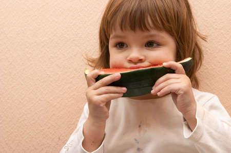 taste of summer - little cute girl eating water melon photo