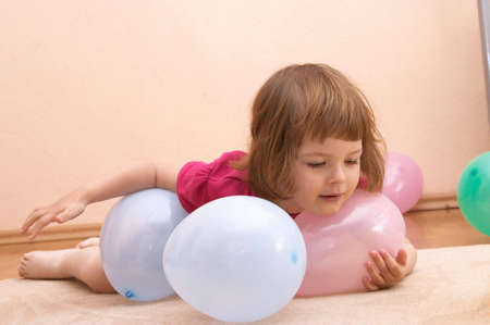 little cute girl playing with colorful balloons photo