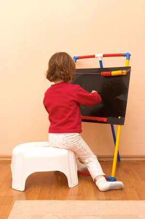 little preschool girl drawing on a blackboard photo