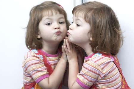 spiegels: kleine, schattige, meisje speelt met haar tweelingzus in de spiegel