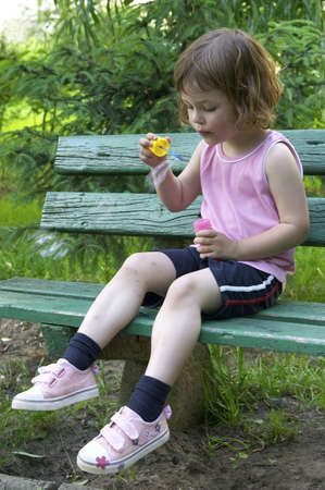 little, cute girl making soap bubbles on a summer day photo