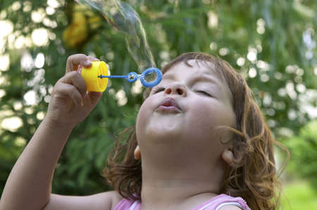 little, cute girl making soap bubbles on a summer day