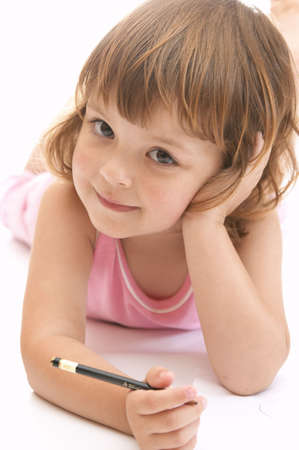 little, cute girl drawing on big white sheet of paper