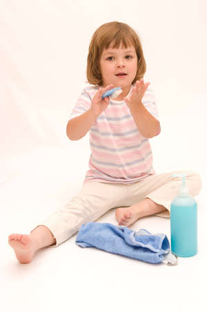 little, cute girl washing her hands with a blue soap and brush Stock Photo - 1342572