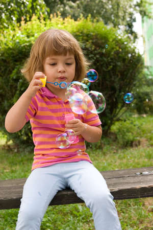 little, cute girl making soap bubbles outdoors photo