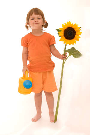 adorable little girl holding big yellow sunflower and watering can