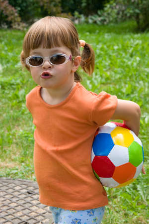ponytails: little, cute girl with colorful football, outdoors Stock Photo