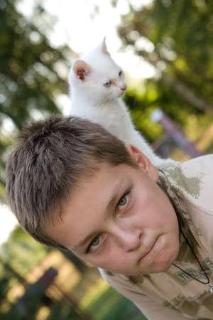 retrato de un niño con su gato escalada en la espalda