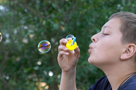 11 years old boy blowing soap bubbles outdoors photo