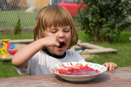 hungry child eating fruit jelly outdoors Stock Photo - 1648496
