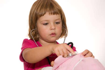 chorowity: mała dziewczynka rozpatrywania jej lalki, odizolowane na białym Zdjęcie Seryjne