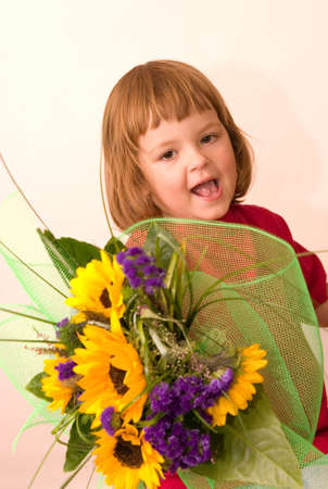 little, cute girl holding big bunch of sunflowers Stock Photo - 1770674