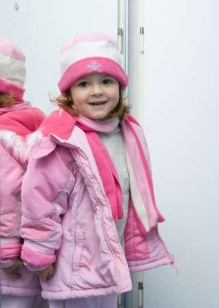 warm jacket: little, cute girl wearing pink winter clothes, soft focus