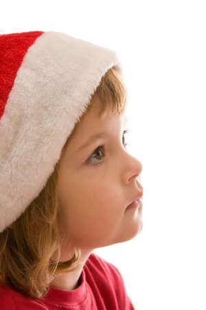 little, cute girl wearing Santas hat, isolated on white