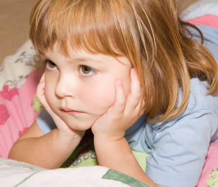 little, cute girl lying in bed and looking poorly