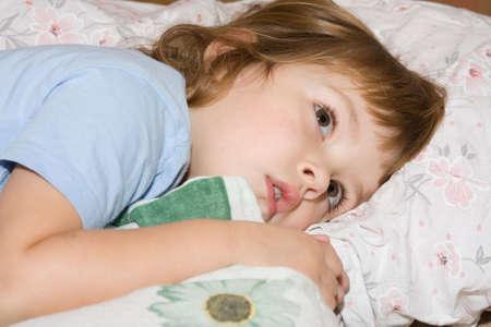 bambini pensierosi: poco, cute ragazza giaceva nel letto e guardando male  Archivio Fotografico