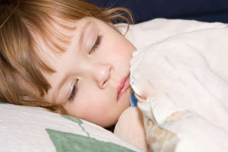 silent night: little cute girl with cuddly toy falling asleep