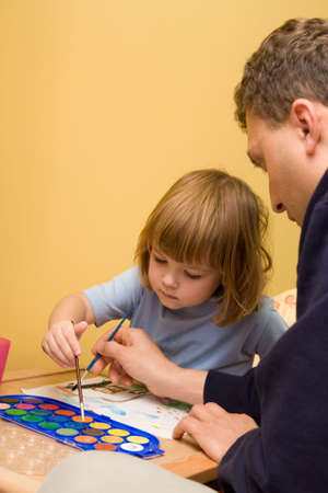 little, cute girl painting with fathers helping hand