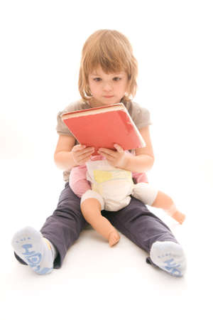 toy story: story time - little girl reading a book to her doll