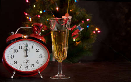 alarmclock: red clock and glass of champagne on Christmas lights background