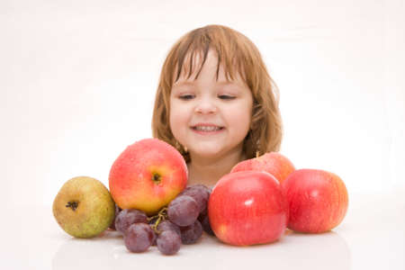 little smiling girl and fruits isolated on white