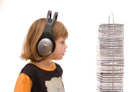 little girl with headphones choosing music, isolated on white photo