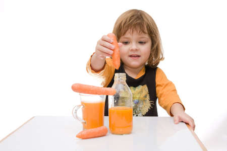 little, cute girl tasting carrot juice isolated on white photo