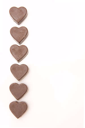 border of little chocolate hearts isolated on white photo