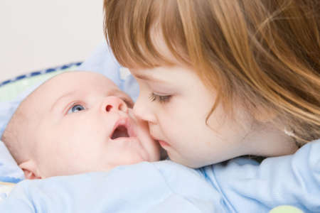cute girl kissing her little brother, close up