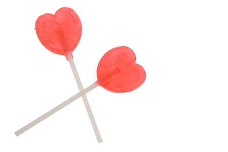 two red heart shaped lollipops isolated on white photo