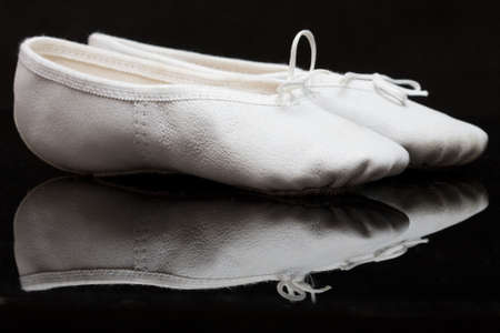 sensible: white childs ballet slippers on black, reflecting background