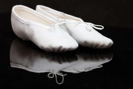 zapatillas ballet: deslizadores del ballet cl�sico del ni�o blanco en fondo negro, de reflejo