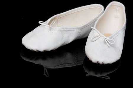 ballet slippers: white childs ballet slippers on black, reflecting background