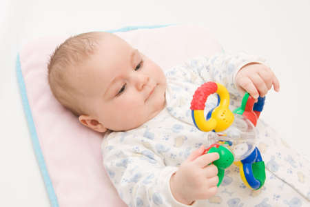 innocense: cute baby boy playing with rattle on light background Stock Photo